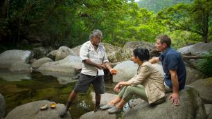 A couple receiving a tour in the jungle by a river